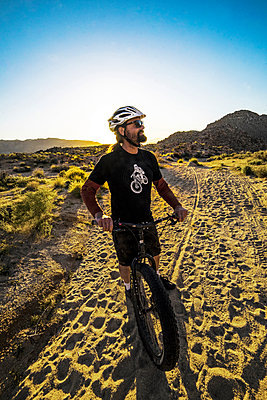 Man with mountain bike standing on trail - p343m1475630 by Cavan Images