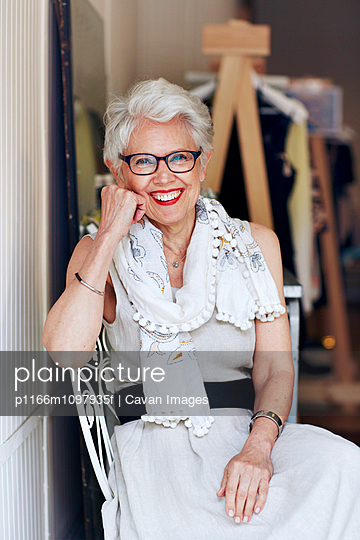 Portrait of senior woman sitting on chair in store - p1166m1097935f by Cavan Images
