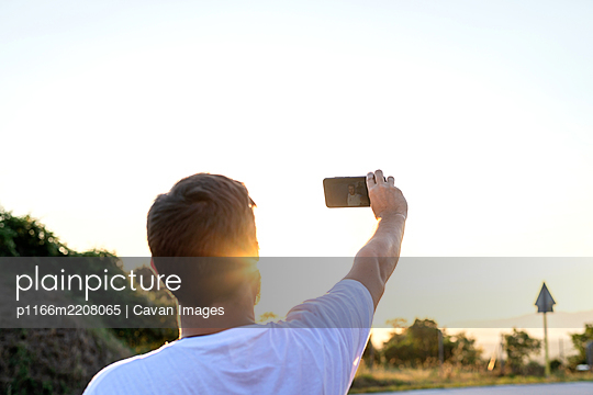 Portrait from behind of man taking selfie during sunset - p1166m2208065 by Cavan Images