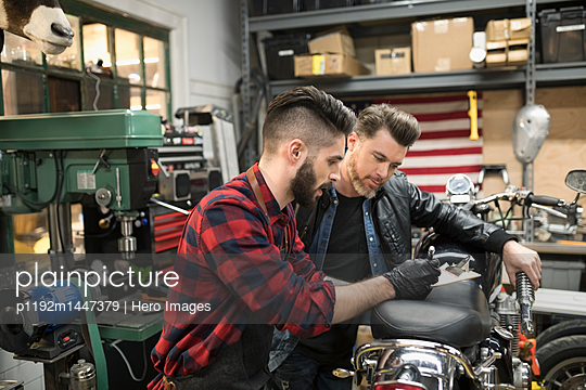 Motorcycle mechanics fixing motorcycle in auto repair shop