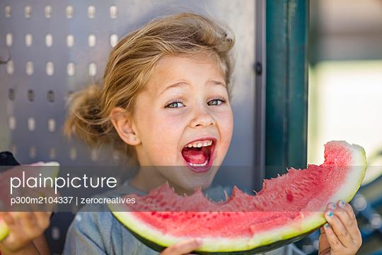 Portrait of happy girl eating a watermelon in kindergarten - p300m2104337 von zerocreatives