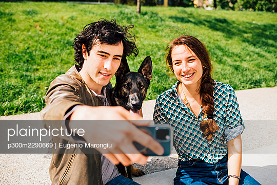 Smiling boyfriend taking selfie with dog and girlfriend through smart phone on footpath - p300m2290669 by Eugenio Marongiu