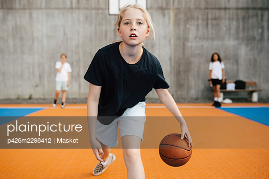 Portrait of female basketball player practicing at sports court - p426m2298412 by Maskot