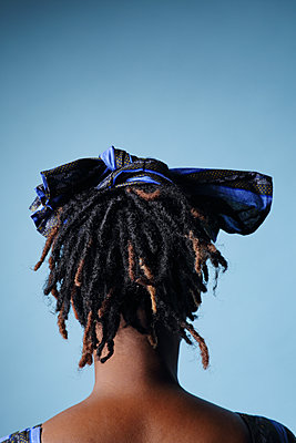 Portrait of a black woman back on a blue background - p1540m2100933 by Marie Tercafs