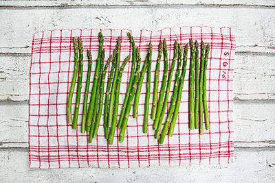 Organic green asparagus on red-white kitchen towel - p300m1587375 von Larissa Veronesi