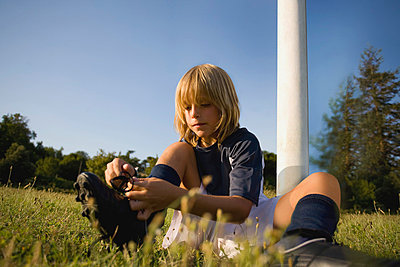Soccer boy tying his shoelaces - p3071208f by Enrico  Calderoni