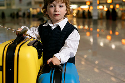 Ein kleiner Junge steht neben Koffern in einer Wartehalle eines Flughafens - p4902204 von Stock4B