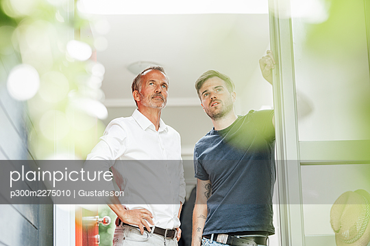 Thoughtful son and father looking away while standing at doorway - p300m2275010 by Gustafsson