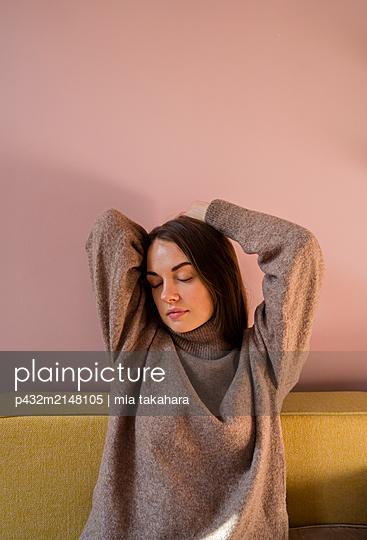Junge Frau entspannt auf Sofa - p432m2148105 von mia takahara
