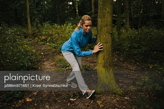 Junge Frau macht eine Dehnübung im Wald - p586m971651 von Kniel Synnatzschke