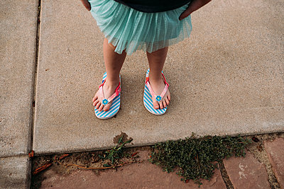 Low section of girl wearing flip-flops while standing on footpath - p1166m2067602 by Cavan Images