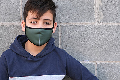 Green eyes boy wearing a green facemask . Coronavirus protection - p1166m2247919 by Cavan Images