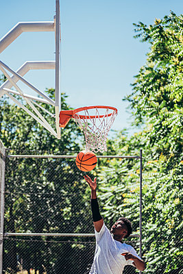 Portrait of a black Afro boy jumping into the basket to shoot the ball. Playing basketball on an urban court. - p1166m2280305 by Cavan Images