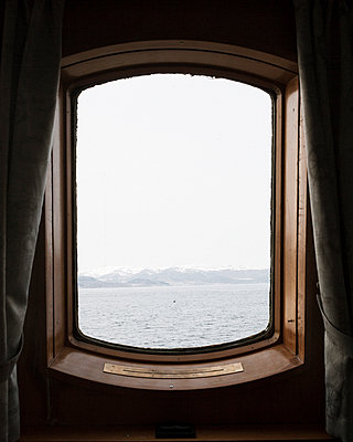View through the cabin window of snow-covered mountains on the shore - p1214m2263136 by Janusz Beck