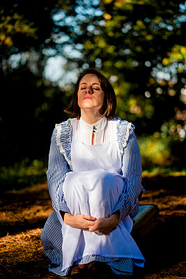 Frau in Dienstmädchenkleidung im Park - p1628m2222176 von Lorraine Fitch