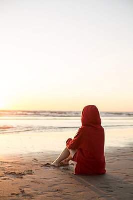 Young woman wearing red hooded jacket sitting on the beach at sunset - p300m2029361 by Jean Schwarz