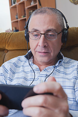 Curious Hispanic man listening to cell phone with headphones - p555m1301698 by REB Images