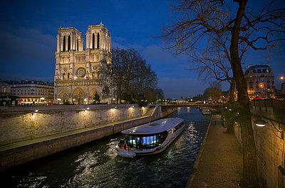 A pleasure boat moves past Notre Dame Cathedral on the Seine River at twilight, Paris, France - p623m1221339 by Frederic Cirou