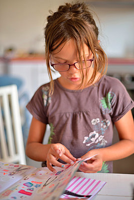 Girl playing with stickers - p885m858308 by Oliver Brenneisen