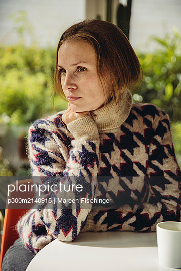 Young woman with glasses wearing fluffy sweater looking sideways - p300m2140915 by Mareen Fischinger
