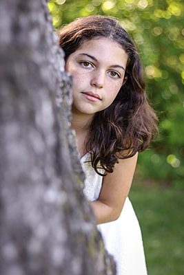 Dark Haired girl looking around tree - p1019m1441644 by Stephen Carroll