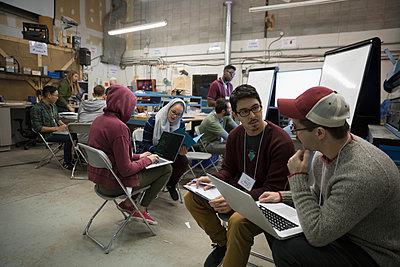 Team of hackers brainstorming using laptop at hackathon in workshop - p1192m1202049 by Hero Images