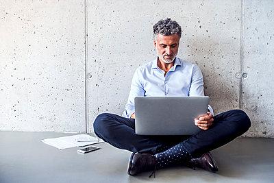 Mature businessman sitting on the floor using laptop - p300m1568082 von HalfPoint
