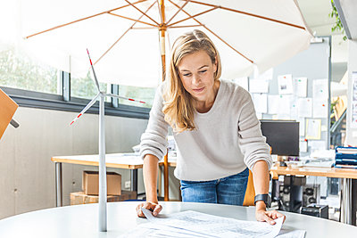 Woman in office working on plan with wind turbine model on table - p300m2070090 by Tom Chance