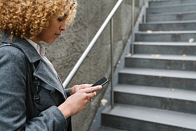 Woman using smartphone at the entrance of a subway station, Berlin, Germany - p300m2143450 by Hernandez and Sorokina
