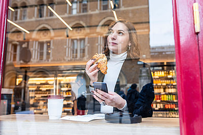 Businesswoman having a snack at a cafe in the city - p300m2181207 by William Perugini