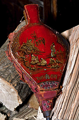 Red bellows with firewood in Cheltenham country home - p349m790913 by Polly Eltes