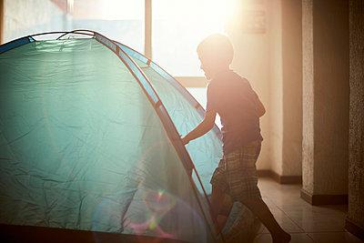 Hispanic boy camping in tent indoors - p555m1304975 by Paco Navarro