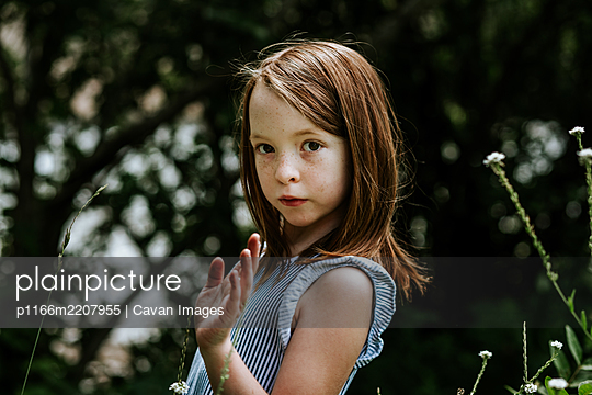 Young girl moving her hand across tall grass on a sunny day - p1166m2207955 by Cavan Images