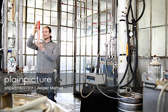 Young male vodka distiller measuring liquid in cylinder in distillery workshop - p924m1022731f by Jesper Mattias