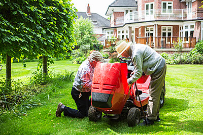 Senior Father and Son fixing together lawn mower - p1026m1164173 by Patrick Frost
