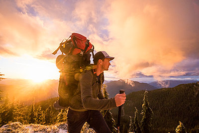 Side view of man backpacking on mountain ridge with scenic view. - p1166m2255895 by Cavan Images