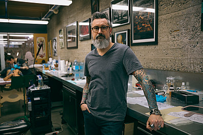Portrait confident tattoo artist in tattoo studio - p1192m1529781 by Hero Images