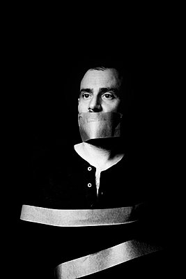 Man with adhesive tape on his mouth - p1521m2150063 by Charlotte Zobel