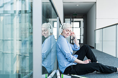 Woman sitting on office floor listening to music with headphones - p300m1580749 von Uwe Umstätter