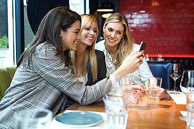 Three happy businesswomen in a restaurant looking at smartphone together - p300m2140239 von Josep Suria