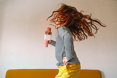 Girl jumping on bed and singing in micro - p300m2198111 by Eloisa Ramos