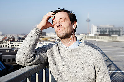 Portrait of man with closed eyes hearing music - p300m2213742 by Jo Kirchherr