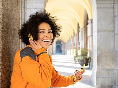 Cheerful woman listening music while using mobile phone standing against pillar - p300m2252604 by Jose Carlos Ichiro