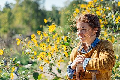 Junge Frau vor einem Feld mit Sonnenblumen - p586m1214252 von Kniel Synnatzschke