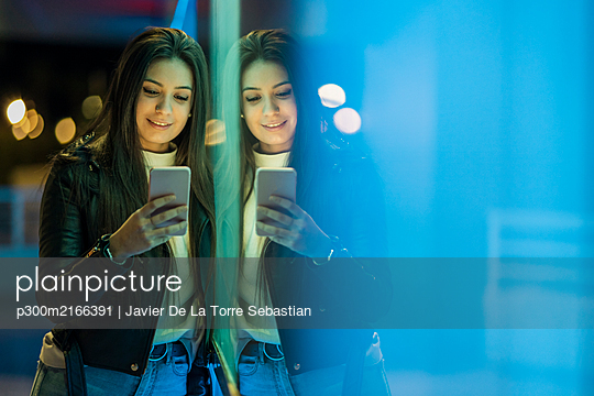 Portrait of smiling teenage girl leaning against glass pane looking at smartphone - p300m2166391 von Javier De La Torre Sebastian