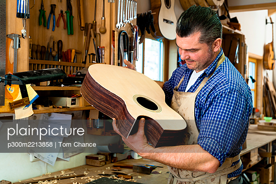 Guitar maker in his workshop - p300m2213858 by Tom Chance