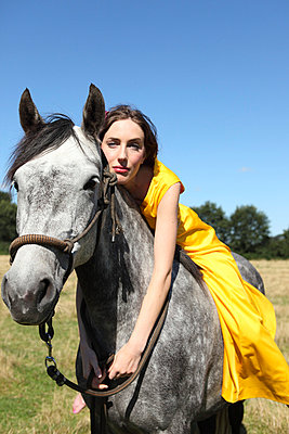 Woman in yellow dress on a horse - p045m721130 by Jasmin Sander