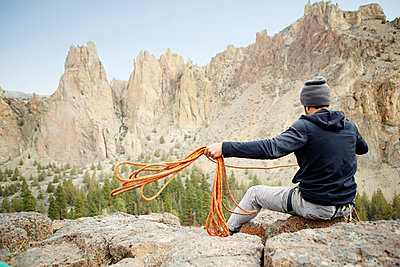 Rear view of rock climber throwing rope while siting on mountain - p1166m1534057 by Cavan Images
