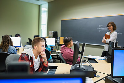 Professor watching college students at computers in classroom - p1192m1036763f by Hero Images