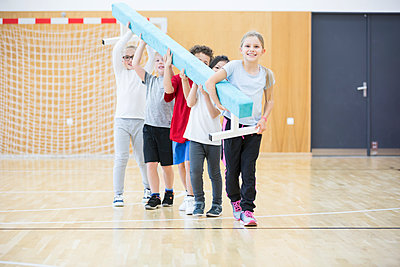 Pupils carrying balance beam in gym class - p300m2005306 von Fotoagentur WESTEND61